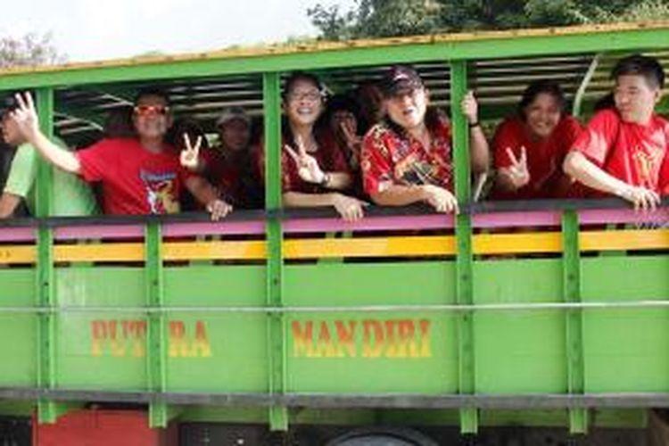 Peserta Asia Pacific Hash 2014 dengan menggunakan truk tiba di Pantai Pede, Labuan Bajo, Kabupaten Manggarai Barat, Nusa Tenggara Timur, Minggu (11/5/2014).