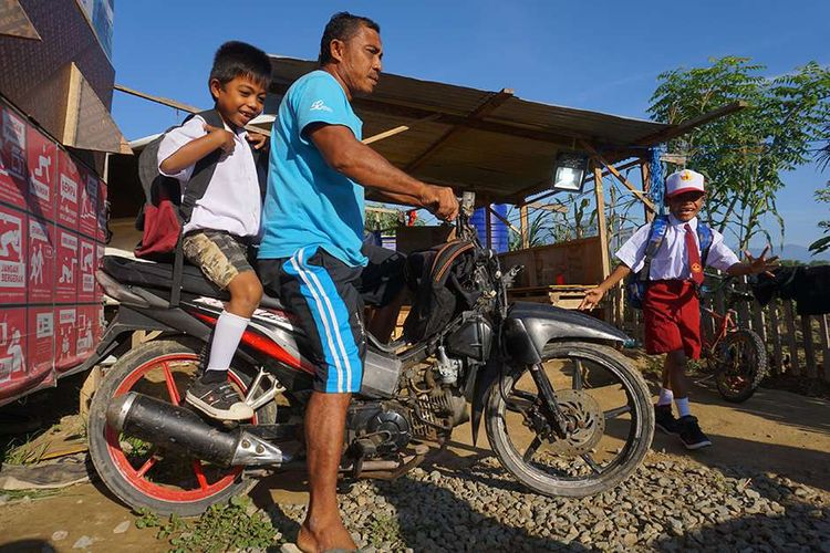 Sejumlah siswa baru bersiap menuju sekolah pada hari pertama masuk sekolah di Kamp Pengungsian Jono Oge, Kabupaten Sigi, Sulawesi Tengah, Senin (15/7/2019). Seluruh siswa SD, SMP dan SMA di daerah terdampak bencana gempa dan likuefaksi tersebut mulai masuk sekolah pada tahun ajaran baru 2019/2020.