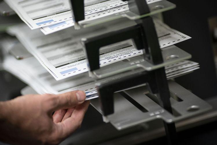 Foto tertanggal 3 November 2020 menunjukkan petugas TPS menyortir surat suara pemilu AS di gedung Kenosha Municipal pada hari pemilihan.