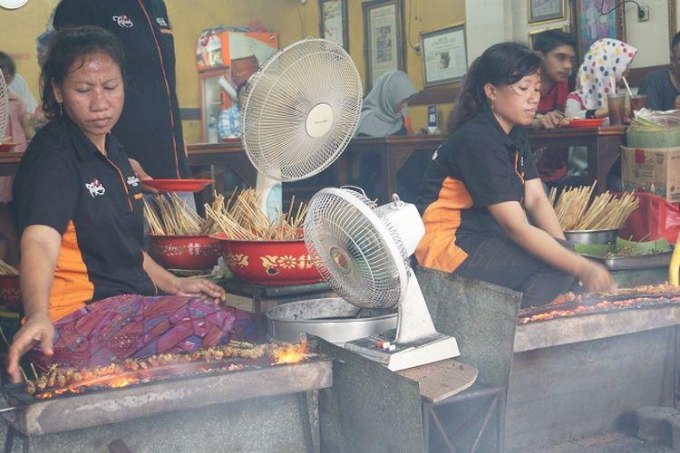 Karyawan Sate Ondomohen Bu Asih sedang membakar puluhan tusuk sate.