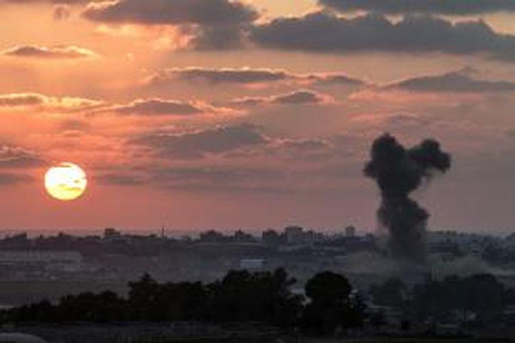 Gambar yang diambil dari wilayah Gaza di teritori Israel ini memperlihatkan asap membumbung di Jalur Gaza, setelah serangan udara Israel pada Rabu (16/7/2014). Pada petang itu, empat bocah yang sedang bermain di pantai setelah menyingkir dari area sasaran gempuran Israel, justru tewas karena serangan Israel ke pantai itu.