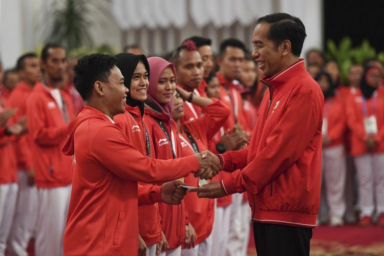 Presiden Joko Widodo (kanan) menyalami dan memberikan buku tabungan kepada lifter Eko Yuli Irawan (kiri) saat pemberian bonus kepada atlet peraih medali di Istana Negara, Jakarta, Minggu (2/9/2018). Pemerintah memberikan bonus kepada para atlet yang berhasil meraih medali dalam ajang Asian Games 2018.