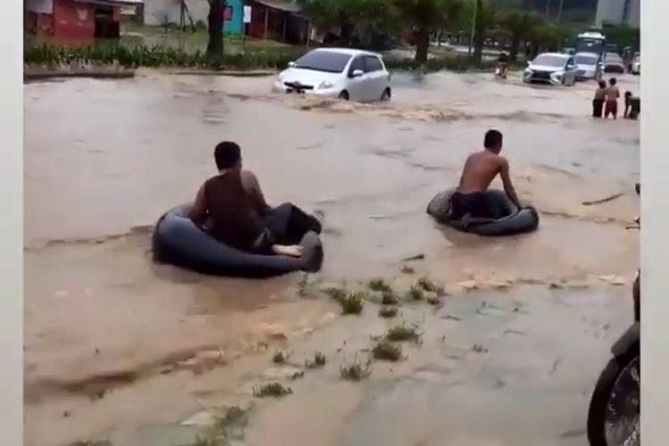 Dua orang warga bermain air menggunakan ban bekas di pinggir Jalan Lingkar Selatan (JLS) Kota Cilegon