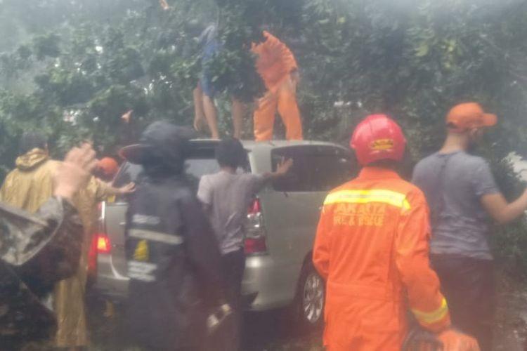 Petugas Damkar Jakarta Timur mengevakuasi pohon tumbang yang menimpa minibus serta merusak instalasi listrik di Jalan Bina Marga Cipayung, Jumat (29/5/2020).