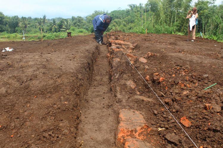 Struktur bata memanjang yang diduga bekas pagar yang ditemukan di sisi selatan area ekskavasi situs suci di lokasi proyek Tol Pandaan-Malang Dusun Sekaran, Desa Sekarpuro, Kecamatan Pakis, Kabupaten Malang, Kamis (21/3/2019)