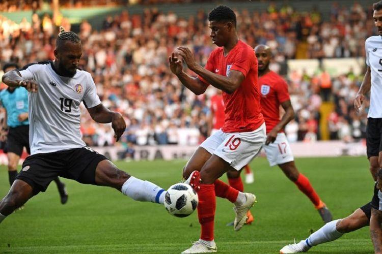 Kendall Waston mencoba menghentikan langkah Marcus Rashford pada pertandingan uji coba antara Inggris dan Kosta Rika di Leeds, 7 Juni 2018.