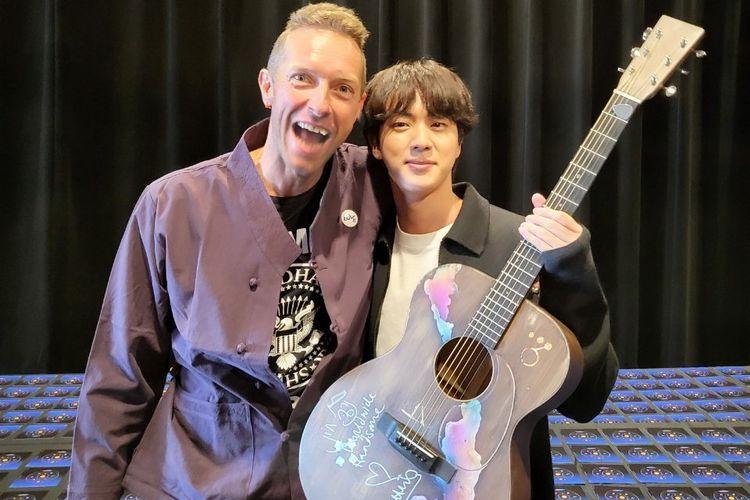 Jin BTS (kanan) berfoto dengan Chris Martin sambil membawa gitar hadiah dari vokalis band Coldplay tersebut.