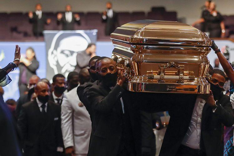 Pallbearer mengangkat peti mati George Floyd saat upacara pemakaman di Gereja The Fountain of Praise di Houston, AS,  Selasa (9/6/2020). Ribuan pelawat baik di dalam tempat penghormatan terakhir hingga di jalanan menuju area pemakaman berbaris seiring peti berlapis emas yang membawa jasad Floyd dibawa menggunakan kereta kuda.