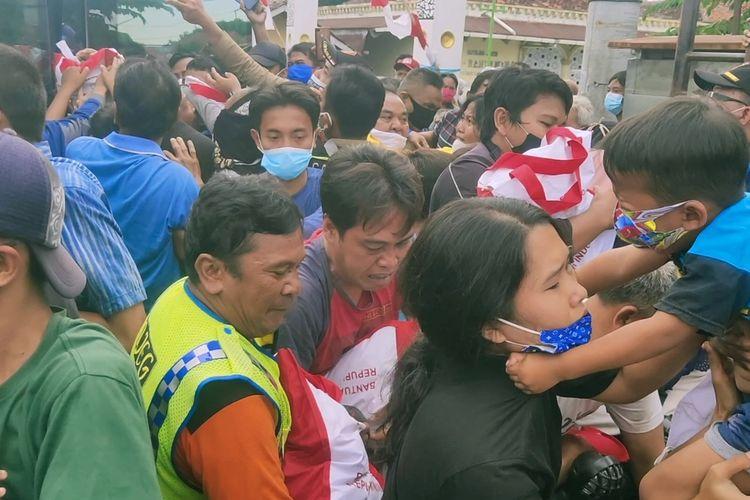 Sejumlah warga berdesakan berebut bingkisan bantuan presiden di jalan Angkasa Raya Bandara Penggung Cakrabuana Kota Cirebon, Selasa (31/8/2021).