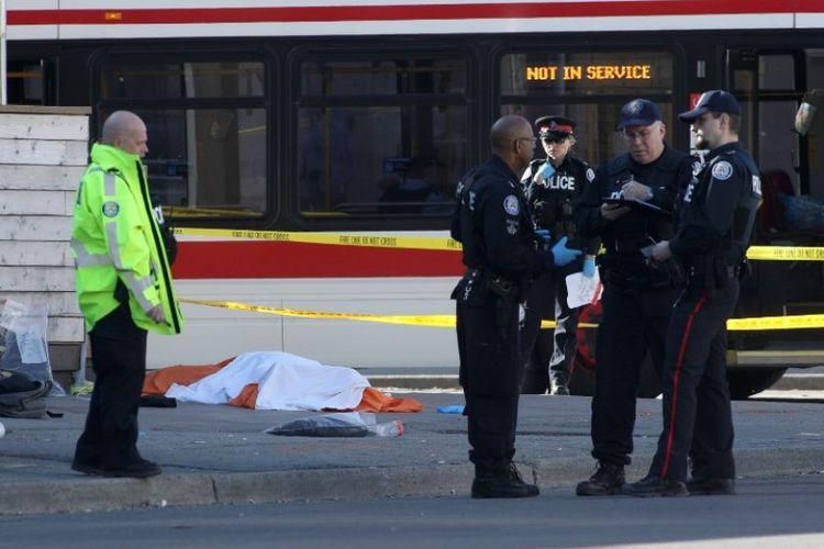 Petugas polisi berdiri di dekat salah satu mayat di jalan, setelah kendaraan melaju di tepi jalan dan menabrak beberapa pejalan kaki di Toronto, Ontario, Kanada, Senin (23/4/2018). (AFP/Lars Hagberg)
