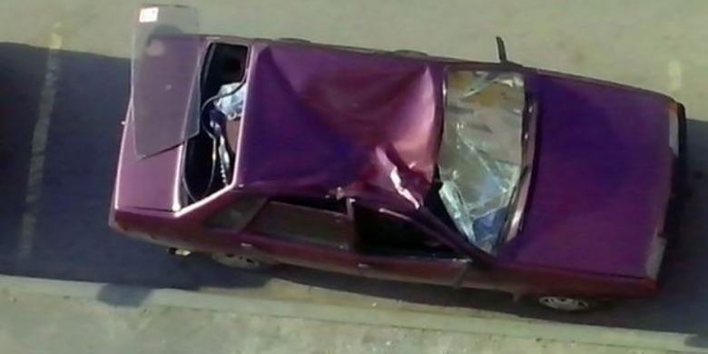 Inilah kondisi mobil yang ditimpa seorang pria yang jatuh dari lantai sembilan sebuah apartemen di kota Yaroslavl, Rusia.