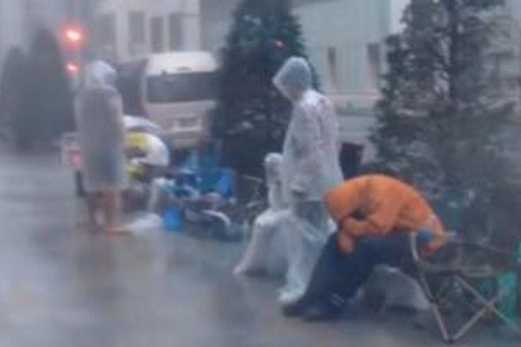 Para pengatri iPhone di Jepang terguyur hujan sebelum dipersilakan berlindung di dalam toko Apple