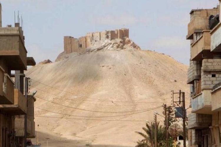 Sebuah benteng yang terlihat dari kota modern Palmyra yang hancur setelah direbut kembali oleh pasukan Suriah dari tangan ISIS, Minggu (27/3/2016).