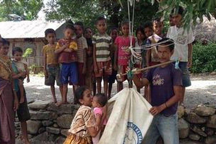 Warga sedang menimbang balita di bawah pohon di Kampung Kofin, Desa Tasinifu, Kecamatan Mutis, Kabupaten Timor Tengah Utara (TTU), NTT.