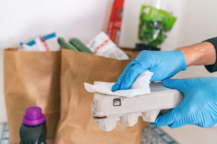 Ilustrasi membersihkan kemasan makanan setelah berbelanja untuk menghindari penularan virus corona yang menyebabkan Covid-19.
