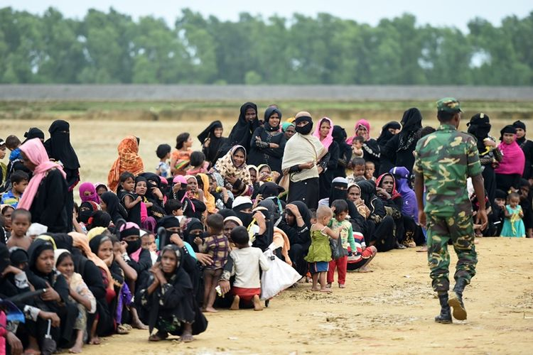 Tentara Bangladesh berjalan di depan para pengungsi Rohingya di kamp Nayapara di Teknaf, Oktober 2017.