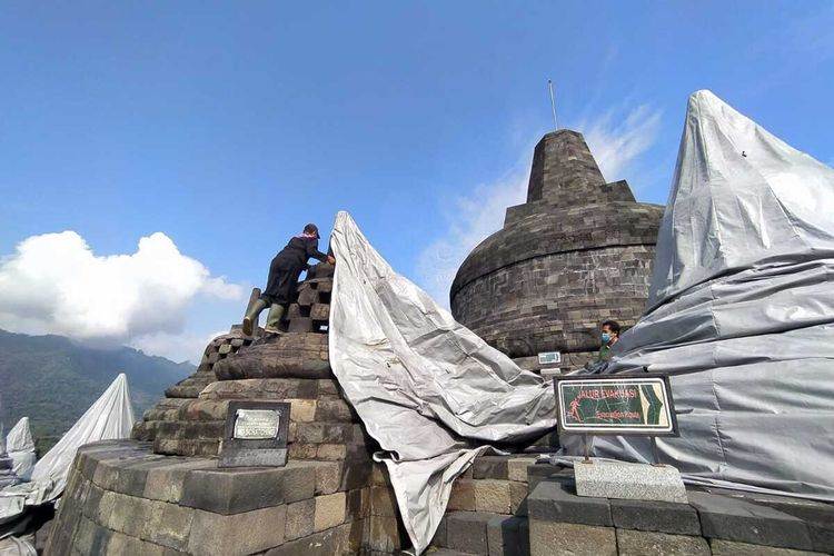 Petugas Balai Konservasi Borobudur membuka plastik yang sejak 7 bulan lalu menutup stupa Candi Boroudur, Magelang, Jawa Tengah, Kamis (10/6/2021).