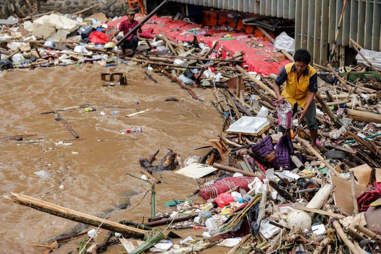 Warga menggambil barang-barang berharga yang terbawa arus di Pintu Air Manggarai, Jakarta, Rabu (7/2/2018). Dinas Lingkungan Hidup dan Kebersihan DKI Jakarta telah mengangkut 1.596 ton sampah yang hanyut akibat air kiriman dari Bendungan Katulampa, Bogor pasca banjir yang melanda Jakarta.