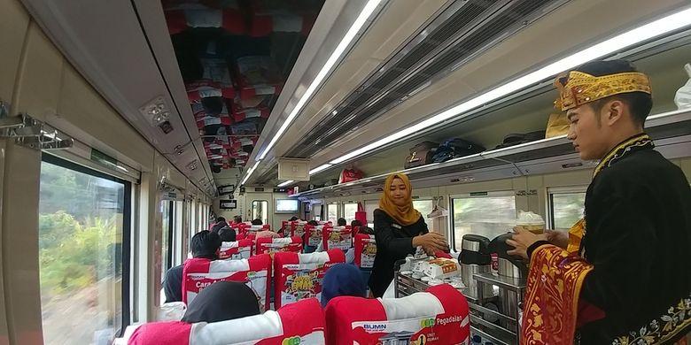 Dua orang petugas kereta api Argo Parahyangan Bandung-Jakarta sedang memberikan layanan restoran pada Sabtu (28/9/2019). PT KAI mengkampanyekan wisata kuliner sebagai bagian dari layanan di dalam kereta.