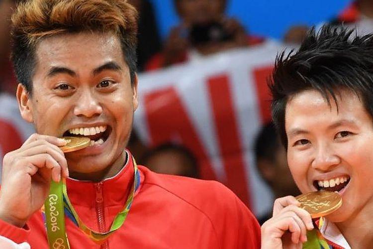 Pasangan ganda campuran Tontowi Ahmad (kiri) dan Liliyana Natsir menggigit medali emas Olimpiade yang diperoleh pada Rabu (17/8/2016) di Rio de Janeiro, Brasil.