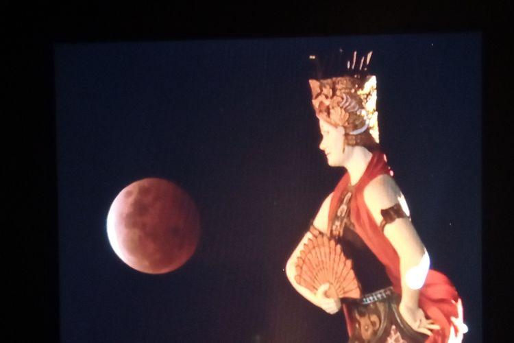 Gerhana bulan total merah nampak dari Monumen Patung penari gandrung, di jalur pantai utara Kabupaten Banyuwangi, Jawa Timur, Rabu (27/5/2021).