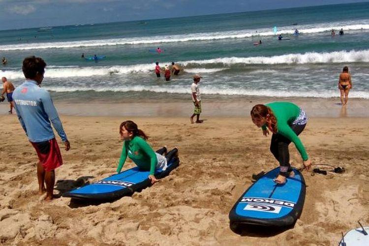 Turis Jepang sedang belajar surfing di Pantai Kuta, Bali.
