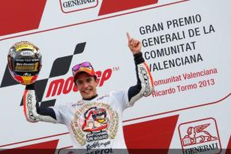 Pebalap Repsol Honda asal Spanyol, Marc Marquez, mengangkat helm juara dunia 2013 saat berada di podium GP Valencia, Minggu (10/11/2013).