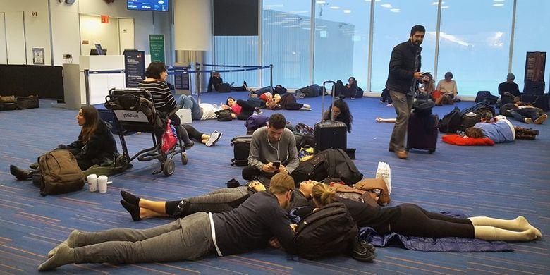 Penumpang menunggu penerbangan yang ditunda di terminal lima, Bandara Internasional John F. Kennedy, di wilayah Queens di New York City, Kamis (4/1/2018). (AFP/Rebecca Butala How)