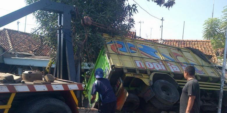 Truk muatan cabai yang terguling di jalur pantura Brebes, Jawa Tengah, diangkat oleh mobil derek, Sabtu (9/11/2013).