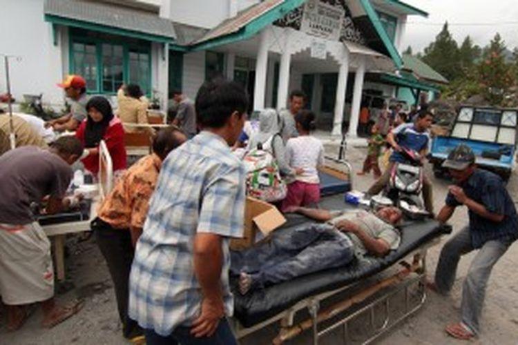 Korban gempa dirawat di luar puskesmas di Kabuoaten Bener Meriah, Aceh, 2 Juli 2013. Gempa berkekuatan 6.2 SR di Aceh, menghancurkan rumah dan mengakibatkan tanah longsor.