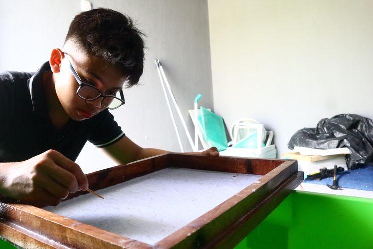 Ahadi Kurniawan (14) sedang mencari plastik yang tercampur dalam cetakan adonan kertas menggunakan pinset. Dia bekerja paruh waktu di rumah produksi kedalang (kertas daur ulang) binaan Pertamina Jambi.