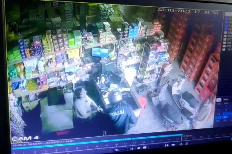 Tangkapan layar CCTV Sebuah aksi percobaan perampokan yang pelakunya mengenakan jaket bertuliskan polisi.