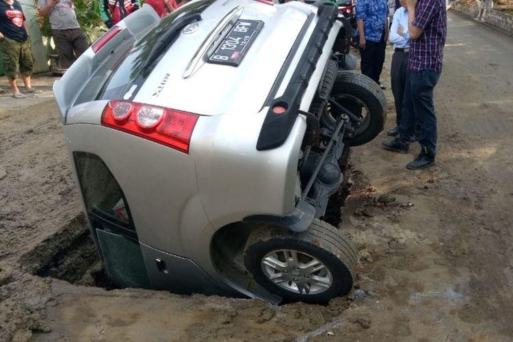 Sebuah mobil Daihatsu Xenia berpelat B 1304 BFW terperosok ke dalam lubang galian resapan air di depan rumah Jalan Susilo I Nomor 26, Grogol, Tanjung Duren, Jakarta Barat pada Minggu (27/5/2018) sekitar pukul 08.30 WIB.