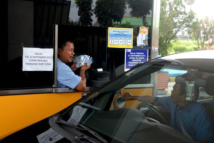 Petugas menawarkan kartau uang elektronik di gerbang pintu tol Jagorawi Citeureup, Kabupaten Bogor, Jawa Barat, Senin (16/10/2017). Sebanyak 1,5 juta uang elektronik  akan dibagikan gratis mulai 16 Oktober hingga 31 Oktober 2017. Masyarakat cukup membayar saldonya saja. Pembebasan biaya kartu ini bertujuan untuk meningkatkan penetrasi pembayaran nontunai di gerbang tol sampai 100 persen. ANTARA FOTO/Yulius Satria Wijaya/kye/17.