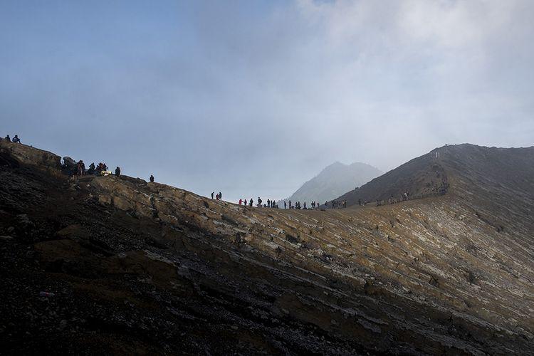 Ratusan wisatawan menikmati pemandangan dari puncak Gunung Ijen, Banyuwangi, Jawa Timur, Sabtu (23/6/2018). Kawah Ijen dengan kedalaman 200 meter menjadi salah satu dari dua lokasi di dunia yang memiliki fenomena api biru selain Islandia, membuat Ijen menjadi tujuan utama pendaki dari berbagai pelosok negeri hingga mancanegara.