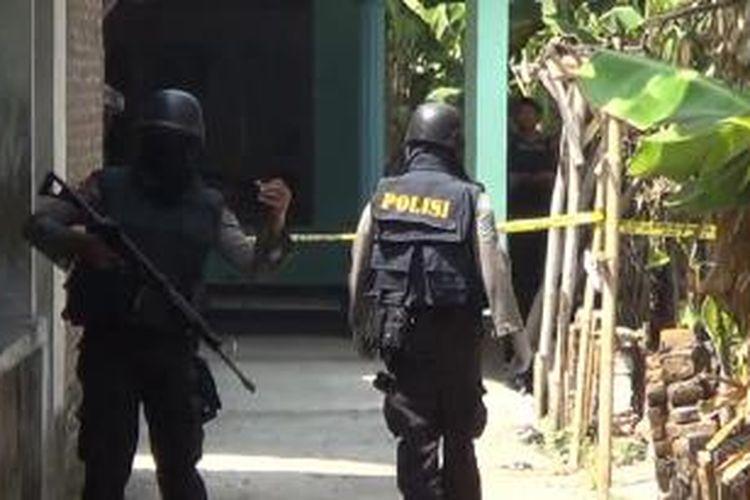 Petugas berjaga di kamar kos di Karanganyar, tempat ditemukannya bom rakitan, Kamis (13/8/2015).