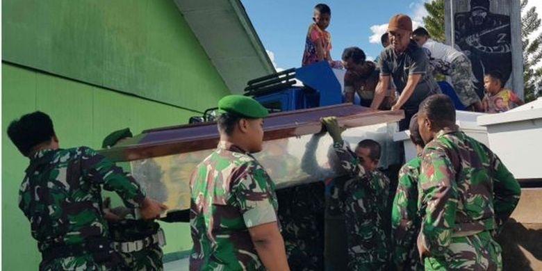 Para personel TNI menurunkan sejumlah peti mati untuk menampung jenazah korban penembakan di Kabupaten Nduga, Papua.