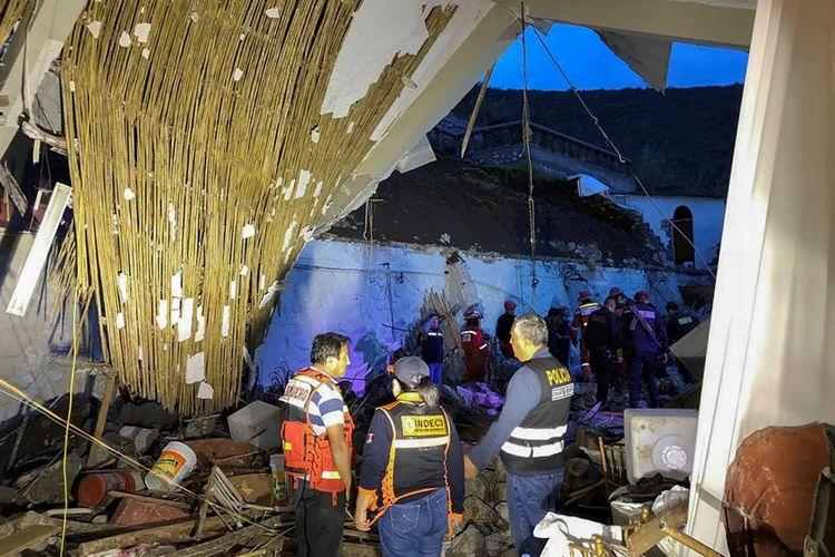 Petugas memeriksa kondisi hotel yang rusak akibat diterjang tanah longsor di Peru, Sabtu (26/1/2019).