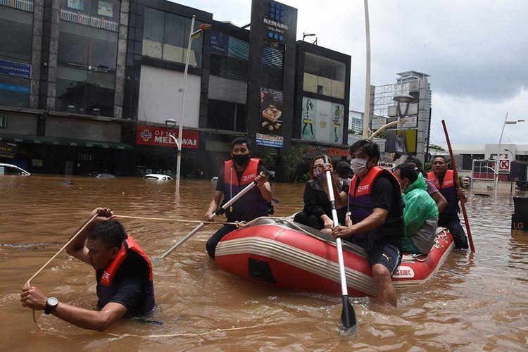Petugas mengevakuasi warga menggunakan perahu karet saat banjir di kawasan Kemang, Jakarta Selatan, Sabtu (20/2/2021). Banjir yang terjadi akibat curah hujan tinggi serta drainase yang buruk membuat kawasan Kemang banjir setinggi 1,5 meter.