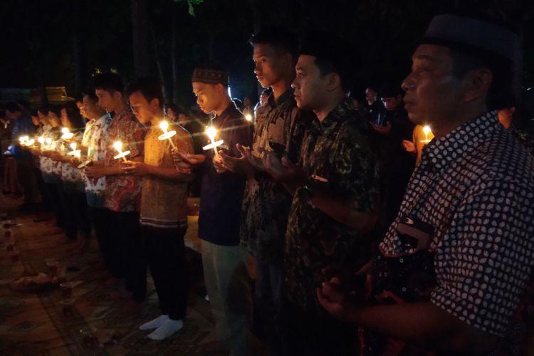 Warga yang Mengikuti Malam Tirakatan Lahirnya Pancasila menyalakan Lilin