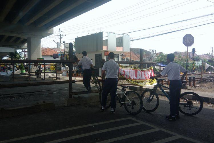 Para pelajar menyeberang perlintasan kereta api yang sudah ditutup di Janti, Yogyakarta.