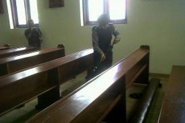Anggota tim Jihandak menyisir tempat duduk jemaah di salah satu gereja di Sumenep, untuk mensterilkan gereka dari segala gangguan, Senin (23/12/2013).
