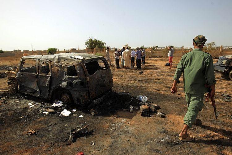Penduduk kota Benghazi melihat lokasi serangan bom mobil yang terjadi di tengah upacara pemakaman mantan komandan pasukan militer Libya, pada Kamis (11/7/2019).