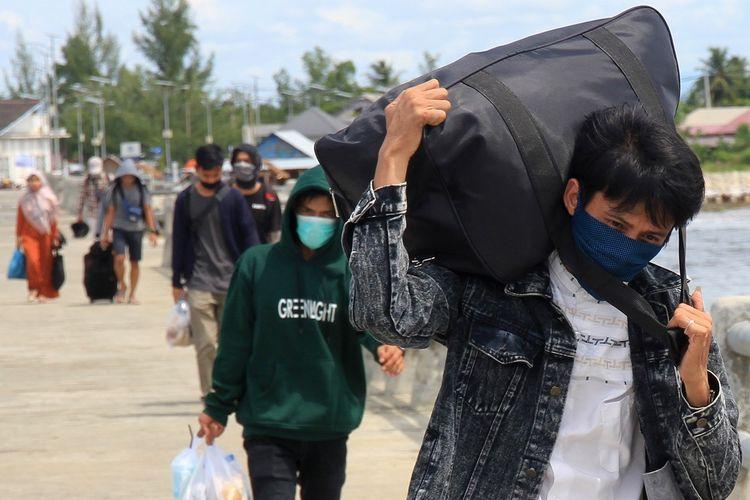 Sejumlah calon penumpang berjalan menuju Kapal Motor Penyeberangan (KMP) Teluk Sinabang di Pelabuhan Penyeberangan Meulaboh-Sinabang Desa Gampong Teugoh, Kecamatan Samatiga, Aceh Barat, Aceh, Senin (30/3/2020). Meskipun Kementerian Perhubungan telah mengimbau masyarakat untuk tidak mudik guna mencegah penyebaran COVID-19, tapi sebagian warga malah antusias untuk pulang kampung guna mengantisipasi jika pemerintah setempat menghentikan pelayaran dan memberlakukan karantina wilayah (lockdown). ANTARA FOTO/Syifa Yulinnas/aww.