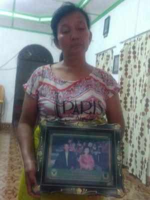 Dameria boru Sidabariba (52), saat menunjukkan foto suaminya, Hotman Nainggolan yang tenggelam di Dsnau Toba, Selasa (19/6/2018).
