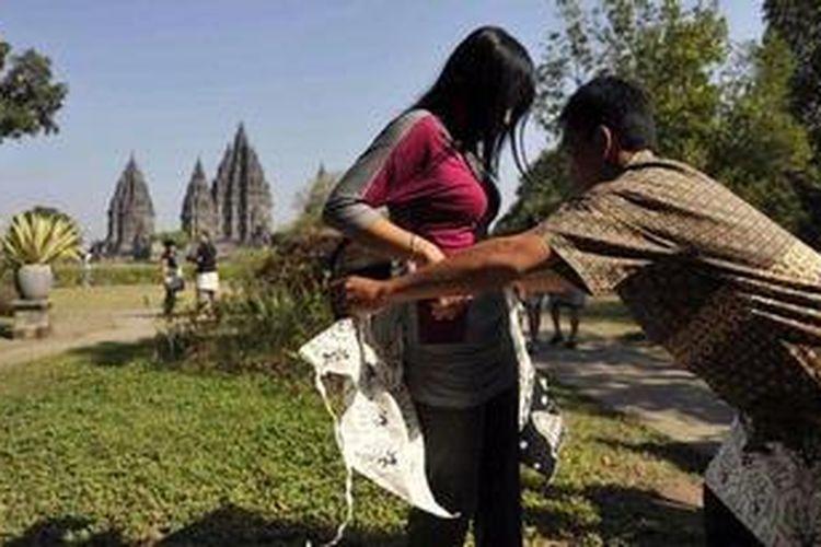 Petugas membantu pengunjung Candi Prambanan, Sleman, DI Yogyakarta, mengenakan sarung batik bermotif Pintu Ratna, Selasa (21/8/2012). Pengelola Taman Wisata Candi Prambanan mulai mewajibkan setiap pengunjung mengenakan sarung batik tersebut sebagai salah satu bentuk penghormatan terhadap tempat sakral bagi umat Hindu tersebut serta untuk melestarikan batik. Pada tahap awal, pengelola tempat itu menyiapkan 5.000 helai sarung batik untuk mendukung program Sarungisasi tersebut.