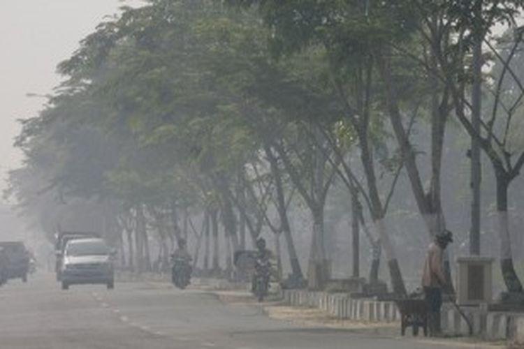 Warga tetap melakukan aktivitas meskipun kabut asap terus menyelimuti kota Pekanbaru, seperti yang tampak di jalan Parit Indah, Jumat (7/8). Kebakaran hutan dan lahan masih terus terjadi di beberapa kota dan kabupaten di provinsi Riau, sehingga menyebabkan ratusan ribu siswa terpaksa diliburkan dari sekolahnya.