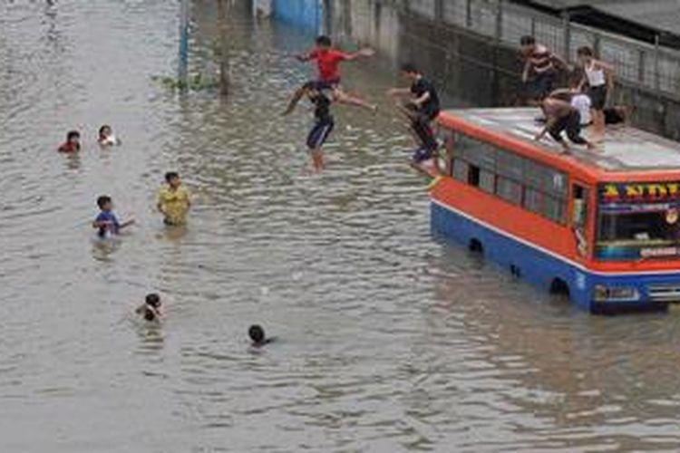 Bagi anak-anak banjir justru menjadi  tempat untuk bermain, seperti terlihat di jalan arteri Puri Kembangan menuju Rawa Buaya, sejumlah anak melompat dari atas metromini ke dalam genangan air, Jumat (18/1/2013).