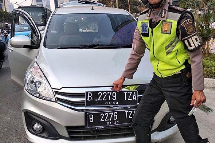 Sebuah mobil yang ditindak polisi pada Kamis (26/7/2018). Dari foto, terlihat mobil yang ditindak menggunakan dua pelat nomor, masing-masing B 2276 TZA dan B 2279 TZA. Tujuannya untuk mengakali peraturan ganjil genap.