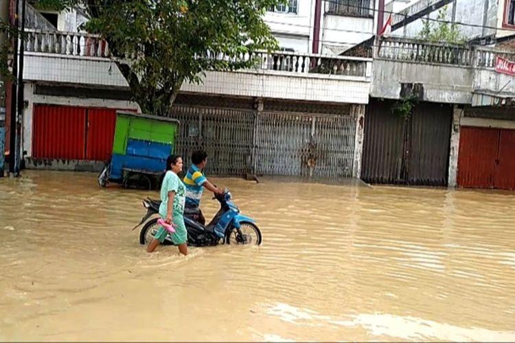Dua orang warga mendorong sepeda motornya yang mogok saat melintasi banjir di Kampung Lalang, Jalan Medan - Binjai. Banjir terjadi di sejumlah titik di Kota Medan dan sekitarnya sejak Jumat (4/12/2020) dini hari.